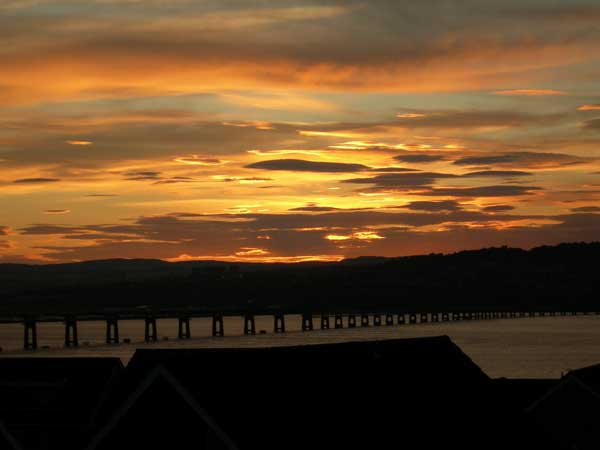 Soft yellow and orange light silhouette the Tay bridge